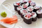 tuna homosaki rolls on a plate with ginger and wasabi