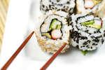 chopsticks picking up a california sushi roll