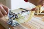 chefs hands rolling a sheet of fresh pasta through a pasta cutter