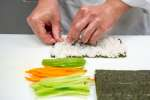 chef's hands preparing a sushi roll