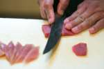 chef's hand thinly slicing tuna