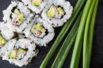 california roll and green onion on a slate plate