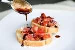 spooning balsamic vinegar over bruschetta