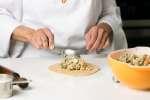 chef filling an empanadad