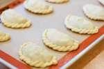 chefs hands folding an empanadas
