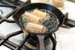 egg rolls frying in hot oil