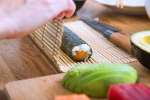 chef rolling sushi on a bamboo mat