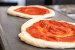 Pizzas With Sauce on Baking Tray