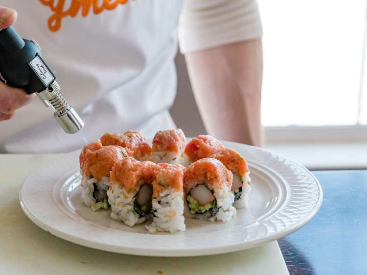 chef torching a salmon roll