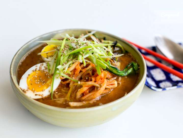ramen noodle soup with eggs and vegetable toppings