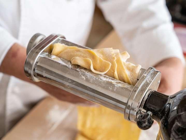 running homemade pasta dough through a pasta roller