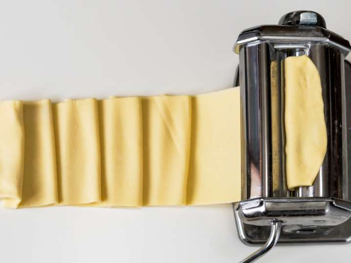 pasta roller with thin sheet of fresh pasta dough