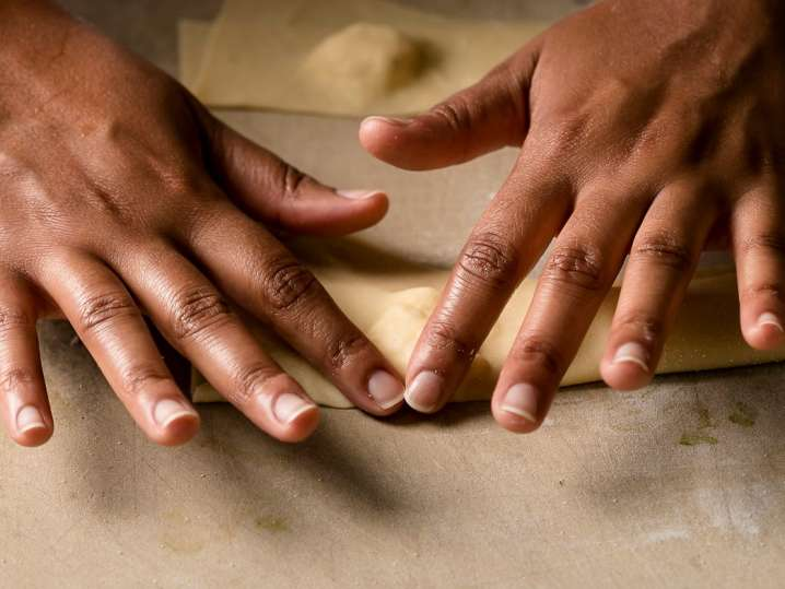 chef hands working with fresh sheet of pasta dough