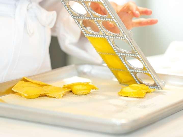 chef using a ravioli press to make homemade ravioli
