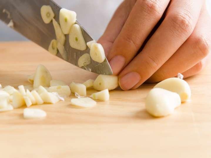 close up of chef chopping garlic