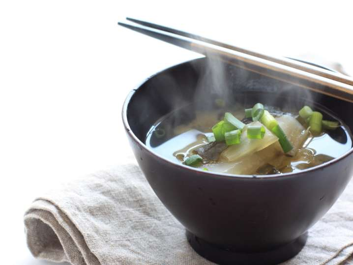 bowl of miso soup with chopsticks