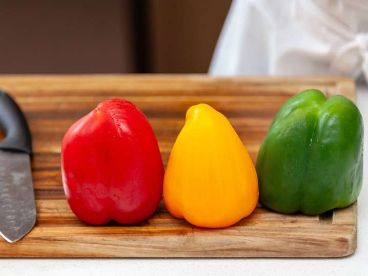 trio of bell peppers lined up on a cutting board