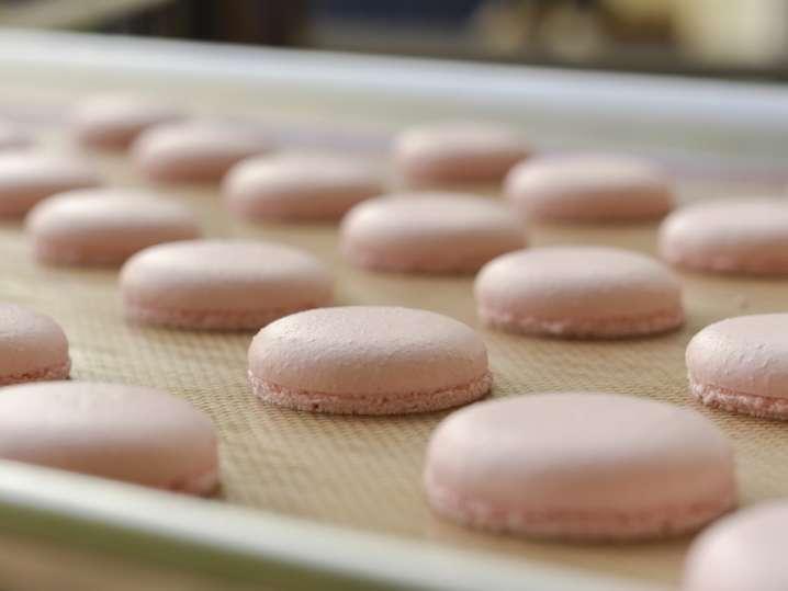 pink macarons on a baking sheet