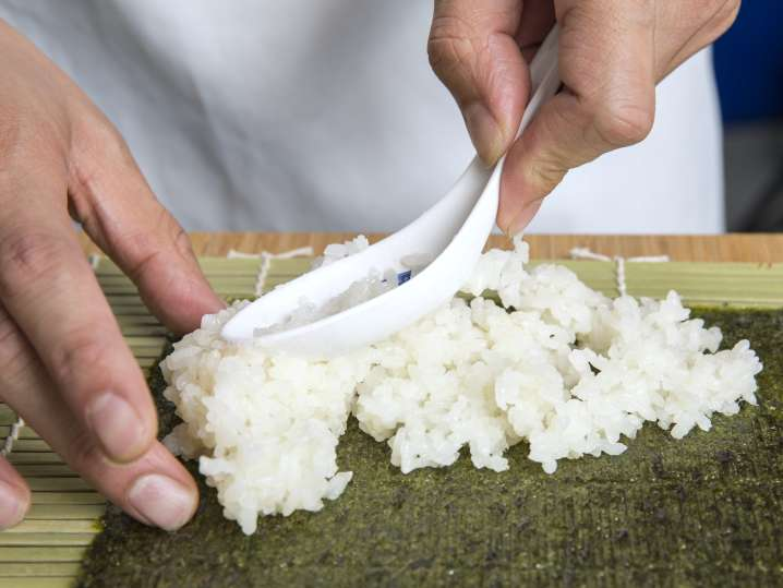 layering rice onto nori for sushi rolls