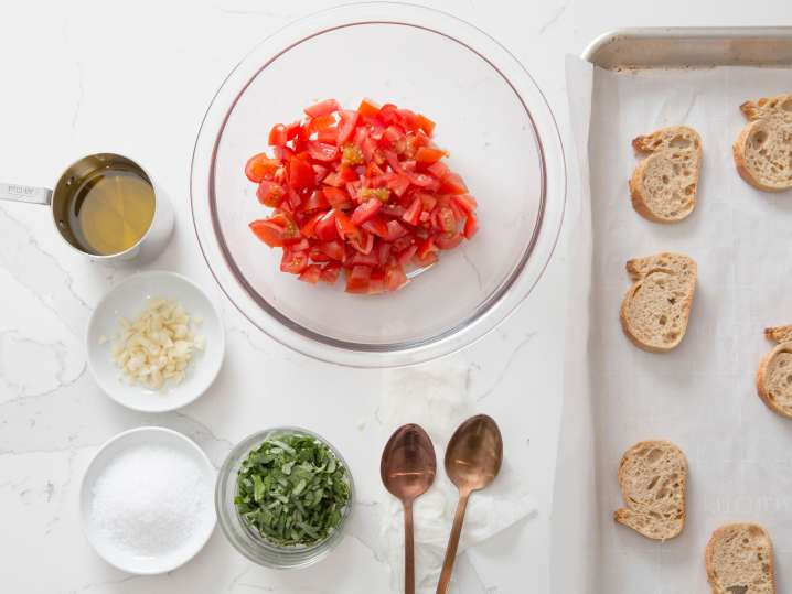 tomatoes, cheese, and bread on a table for making bruschetta