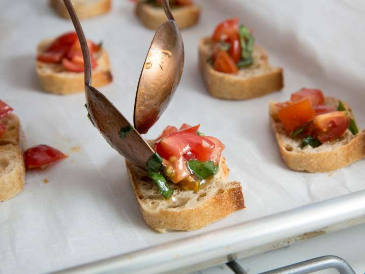 close-up of spoons plating bruschetta on a baking tray