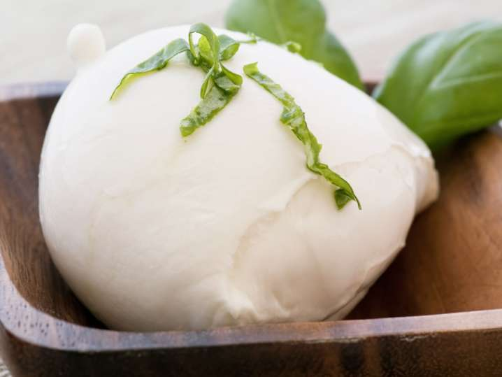 ball of mozzarella in a bowl with fresh basil