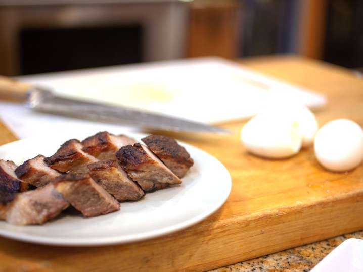 cutting board with pork belly and hard boiled eggs