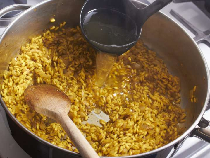 stirring stock into risotto milanese