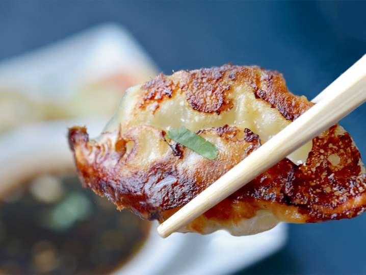 person eating a homemade dumpling with chopsticks