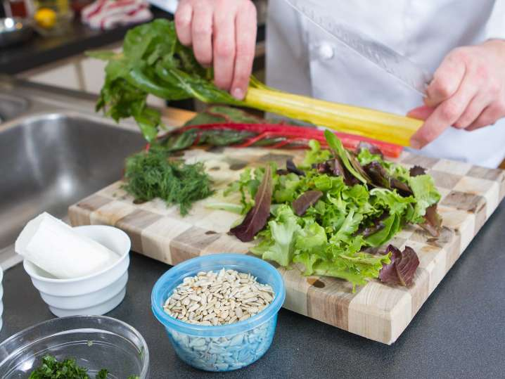 chef chopping vegetables and salad greens on a cutting board