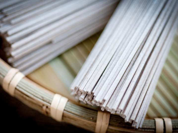 uncooked rice noodles on a bamboo mat