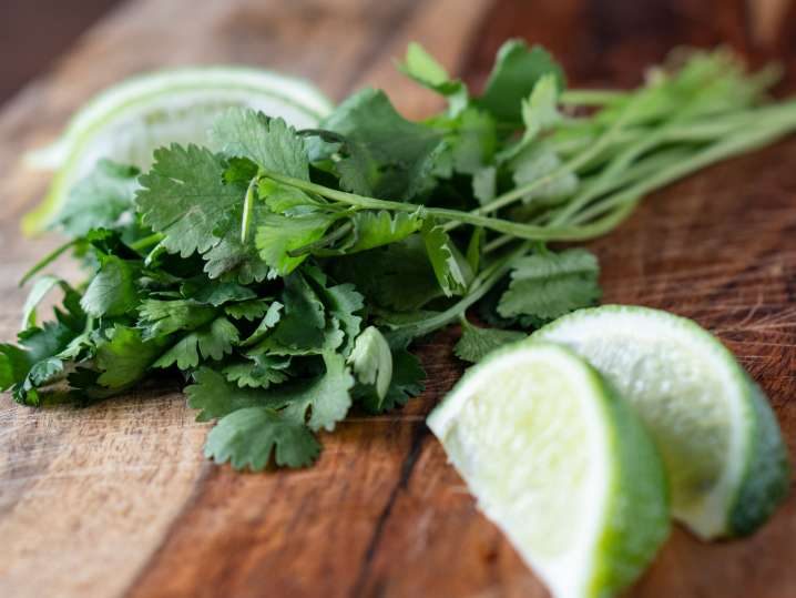 cilantro and lime wedges on a cutting board