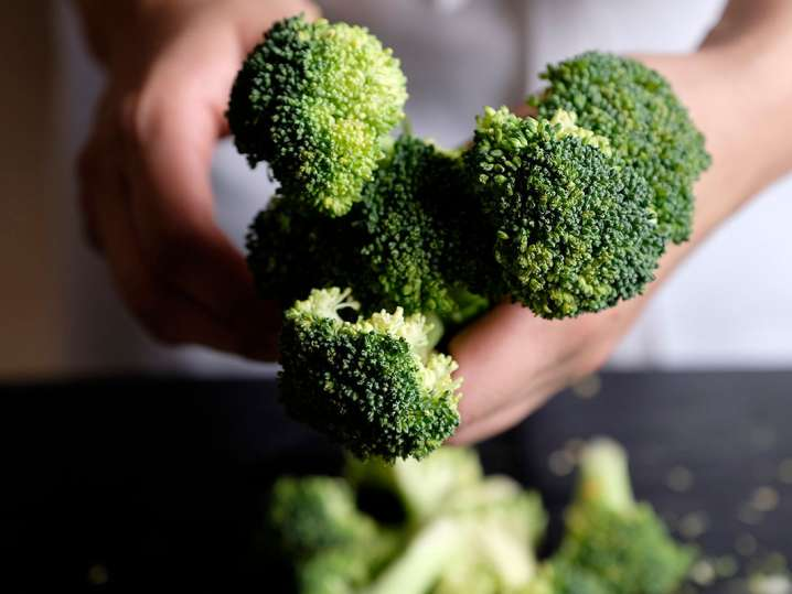 chef's hands holding broccoli