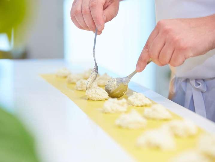spooning ricotta filling into ravioli