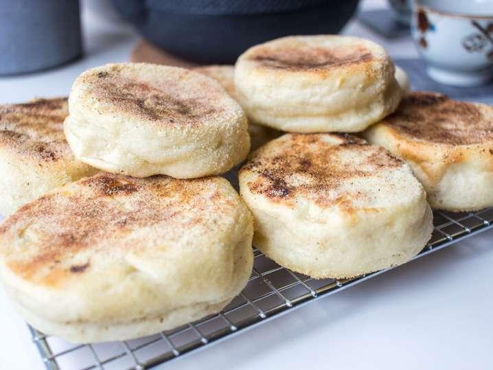 chef hands spooning hollandaise over eggs benedict