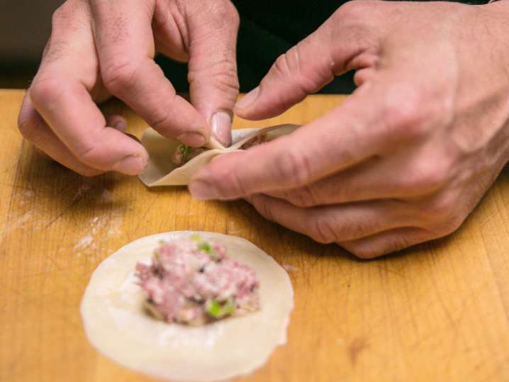 chef's hands filling wonton wrappers to make potstickers