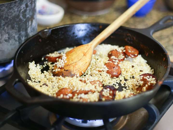 wooden spoon stirring paella rice with sausage