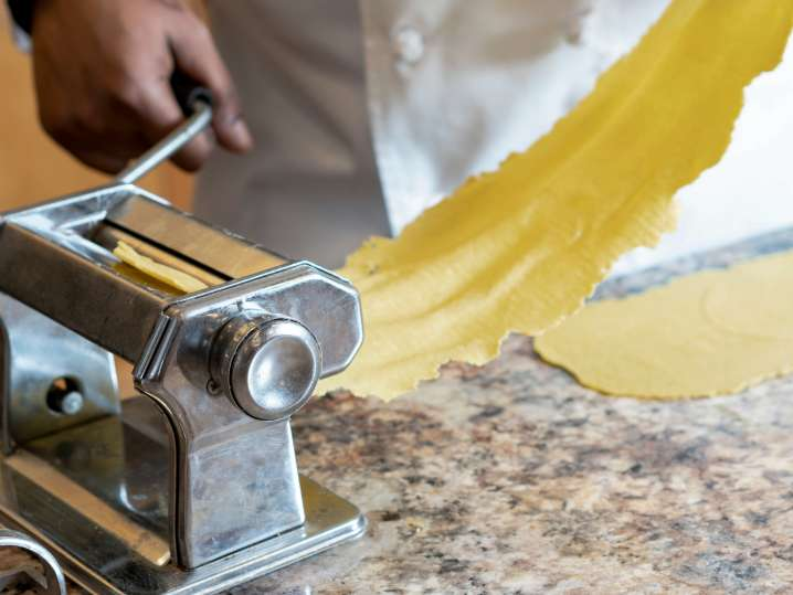 chef rolling sheet of fresh pasta dough