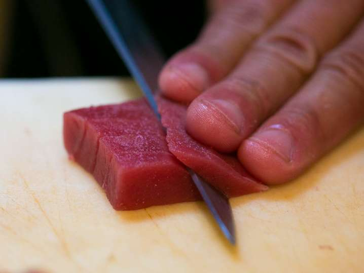 chef slicing fresh tuna to make sushi