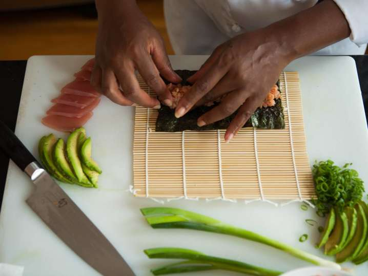 chef's hands preparing a tuna roll on a bamboo mat
