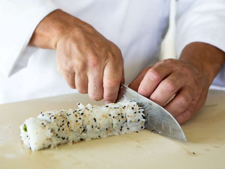 chef slicing a sushi roll