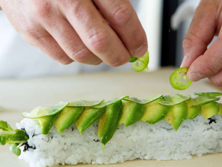 putting avocado slices on a caterpillar roll