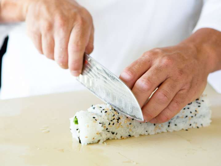 chef slicing california sushi roll