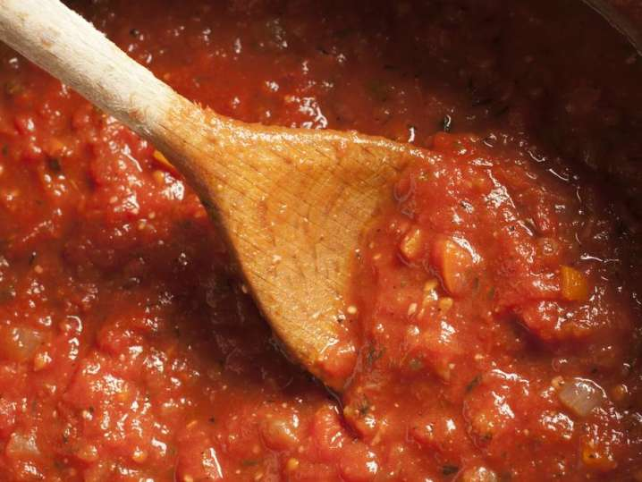 wooden spoon stirring pot of pasta sauce