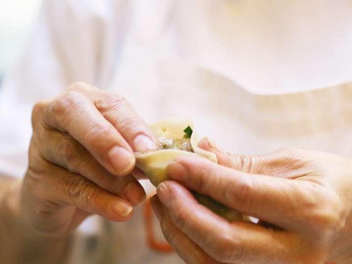 chef filling and folding a wonton wrapper to make gyoza