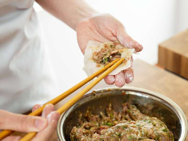 chef filling a wonton wrapper with potsticker ingredients