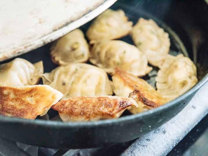 potstickers frying in a cast iron pan