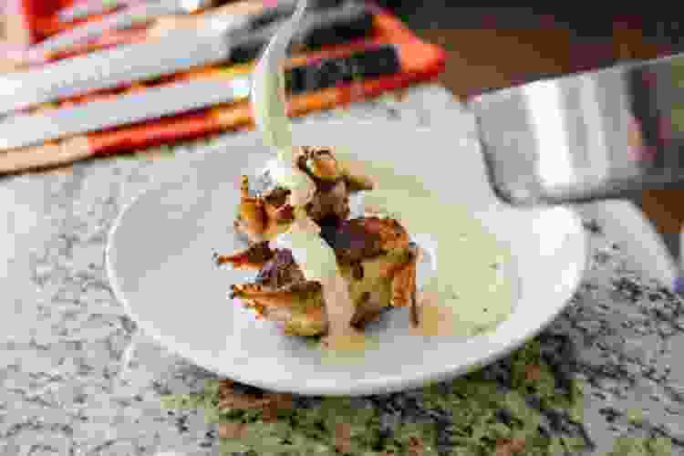 chef plating chicken with cream sauce