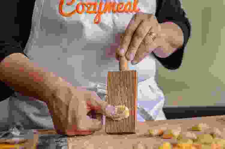 chef rolling gnocchi down a wooden gnocchi board
