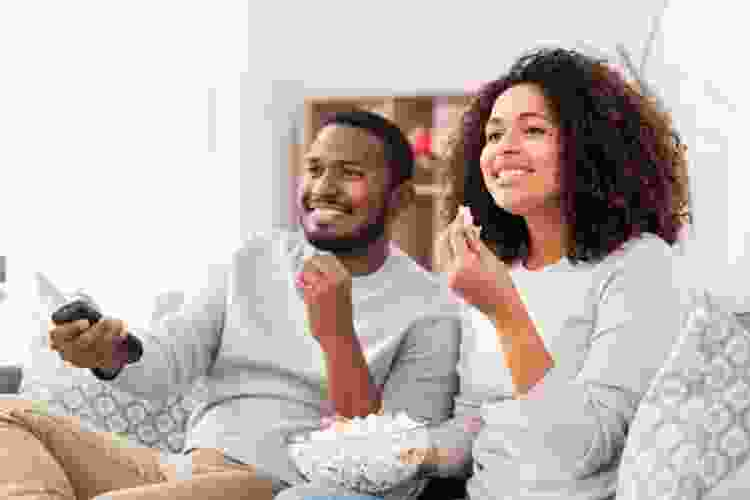 young couple watching tv on the couch with popcorn
